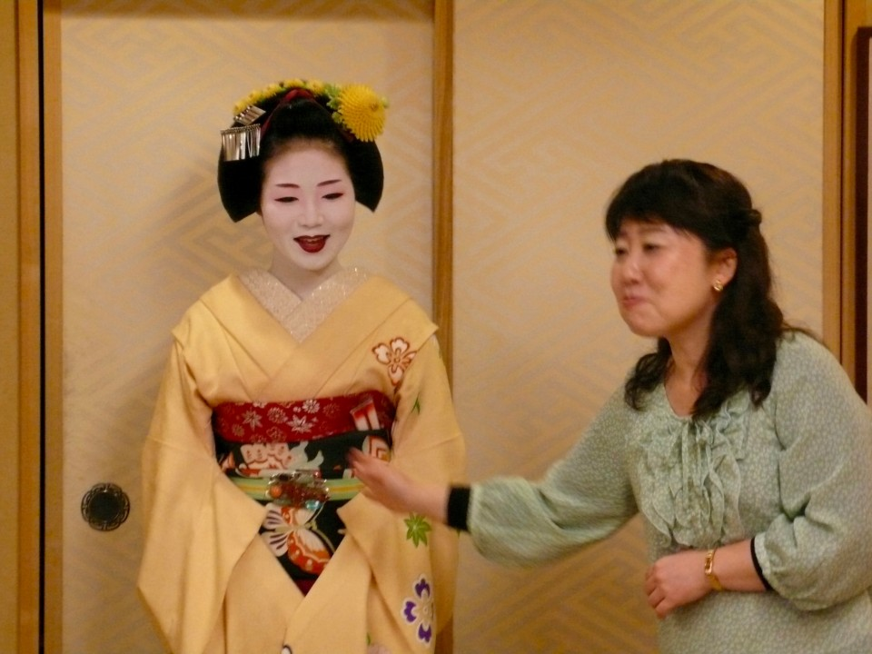As the Geiko played and sang, this lovely MAIKO danced for us.  Maiko is a young woman under 21 in training to become a Geisha.  At 21, a Maiko must decide if she will continue to train to become a Geisha. This young woman will decide next year if she wants to continue her path to becoming a Geisha/Geiko.  If she does, she will choose not to marry.  She lives in a house with other MAIKO.  They have a house mother.  After she danced for us, Chiaki translated for her as we asked many questions about her life.  The Maiko-san had a beautiful way about her. She is the embodiment of grace and all the kindness that is Japan.  She also came around to our table and spoke to individuals.  She spoke beautiful English. By the way, this is her own hair!  She spends hours dressing in kimono and doing up her hair (once a week) and putting on her make-up (daily) and learning the arts.  She has two days off per month. We asked her what she likes to do on her day off?  She wears jeans and wears her long hair loose past her shoulders and goes to the movies with her friends, who are other maiko!  She travels dressed like this, always in the company of her female escort, the house mother, to various places of entertainment AND to other countries (yes, she dressed like this on flight...always with a female escort.) Only one man is allowed to enter the MAIKO/Geisha house and it is the one man who ties her OBI (waist ban). Why a man to tie the obi?  Because he has to pull it tight and has the strength to pull it and tie it!