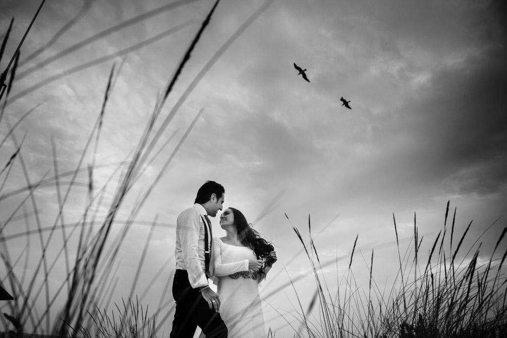 fotos de boda en la playa con una pareja que vuela alto