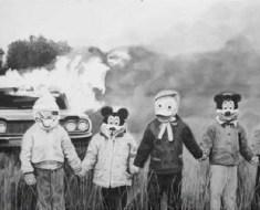 Burning car and children wearing masks