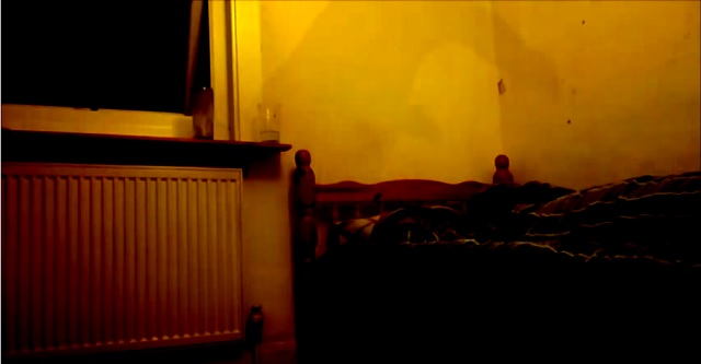 Shadow person over top bed at night