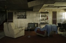 The lower level of an abandoned home with mid century decoration and furniture.