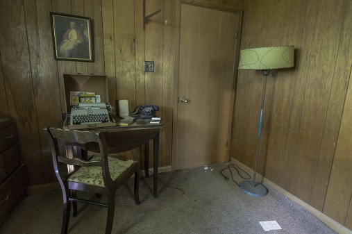 Inside this abandoned house sits an office, with a photo of the Pope on the wall