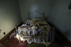 The still made bed inside an abandoned ontario house.