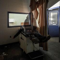 a ghostly figure in the medical exam room in an abandoned factory