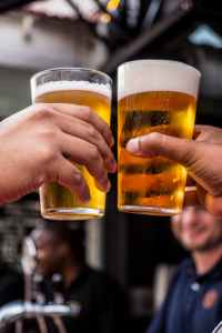 two persons holding drinking glasses filled with beer