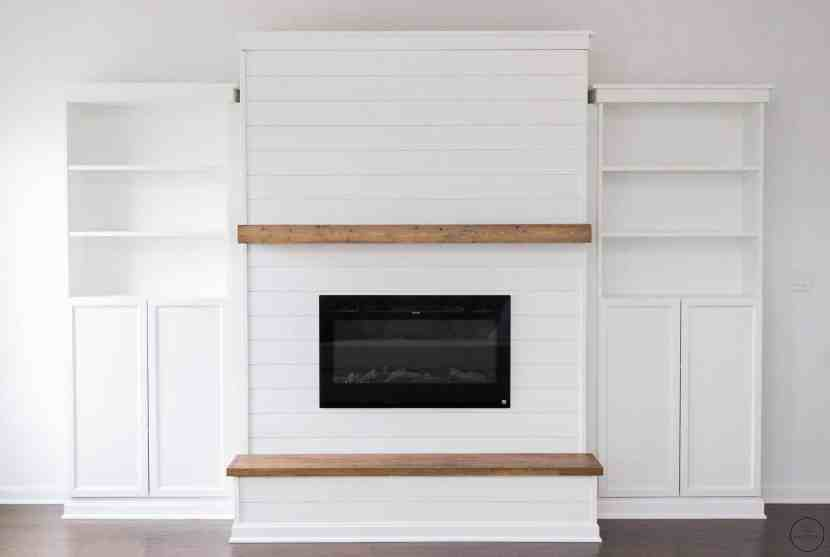 a modern farmhouse electric fireplace feature wall with built-in bookcases from IKEA, a floating mantle, and a wooden hearth