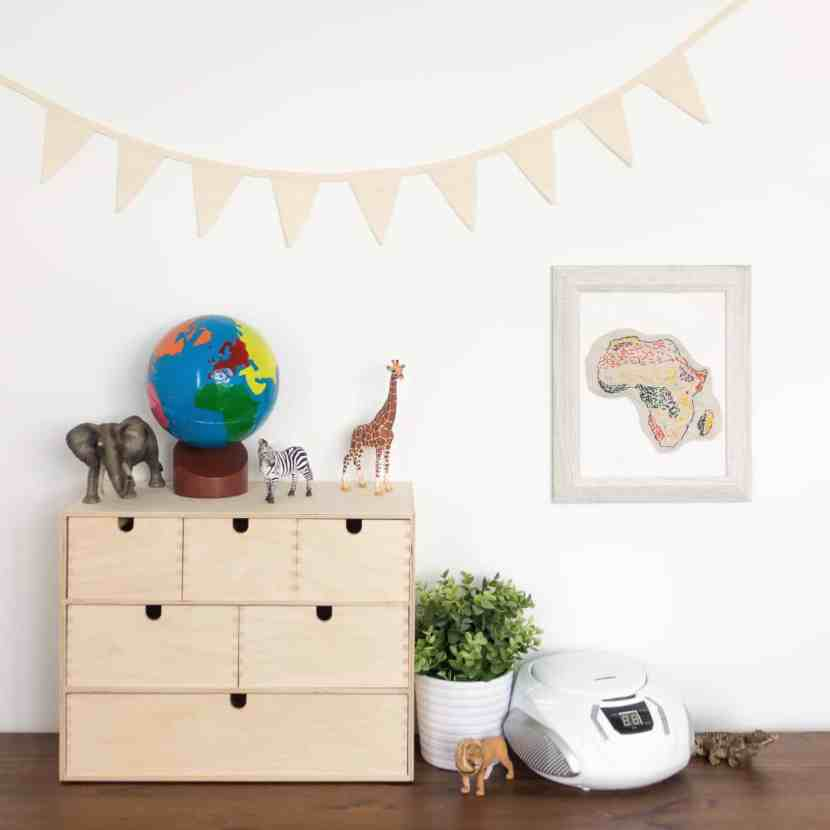 A continents globe sits on top of a Moppe storage unit from IKEA. An embroidered biome map sewn by a child is hung on the wall, and several Schleich animals are displayed beside it, inviting open-ended play and exploration for young children.