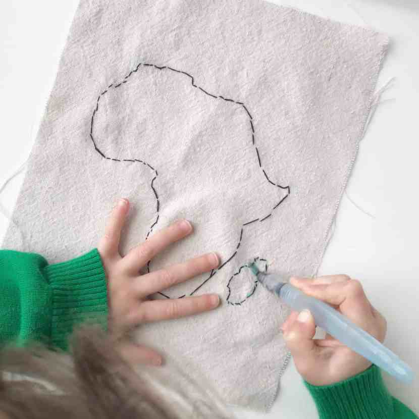 A water brush can be used to erase the fabric template lines on an embroidery project with kids.