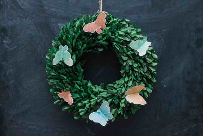 close-up view of preserved boxwood wreath with watercolor butterflies hanging on a chalkboard