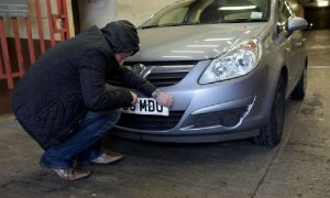Man removing car number plates