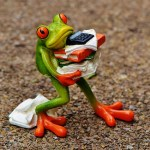toy frog holding a falling stack of papers