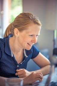 woman smiling at her laptop while using FreeConference.com for screensharing