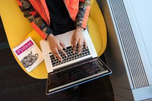 _Overhead view of woman's hands typing at laptop, seated on yellow chair, working on coding file with a textbook beside her