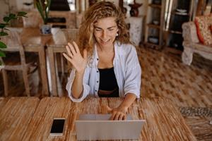 Happy woman sitting at table smiling, and waving at laptop while engaged in a video conference