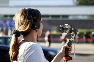 Side view of woman wearing headphones recording outdoors, holding mobile phone mounted to stabilizer