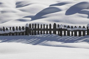 fence submerged in snow