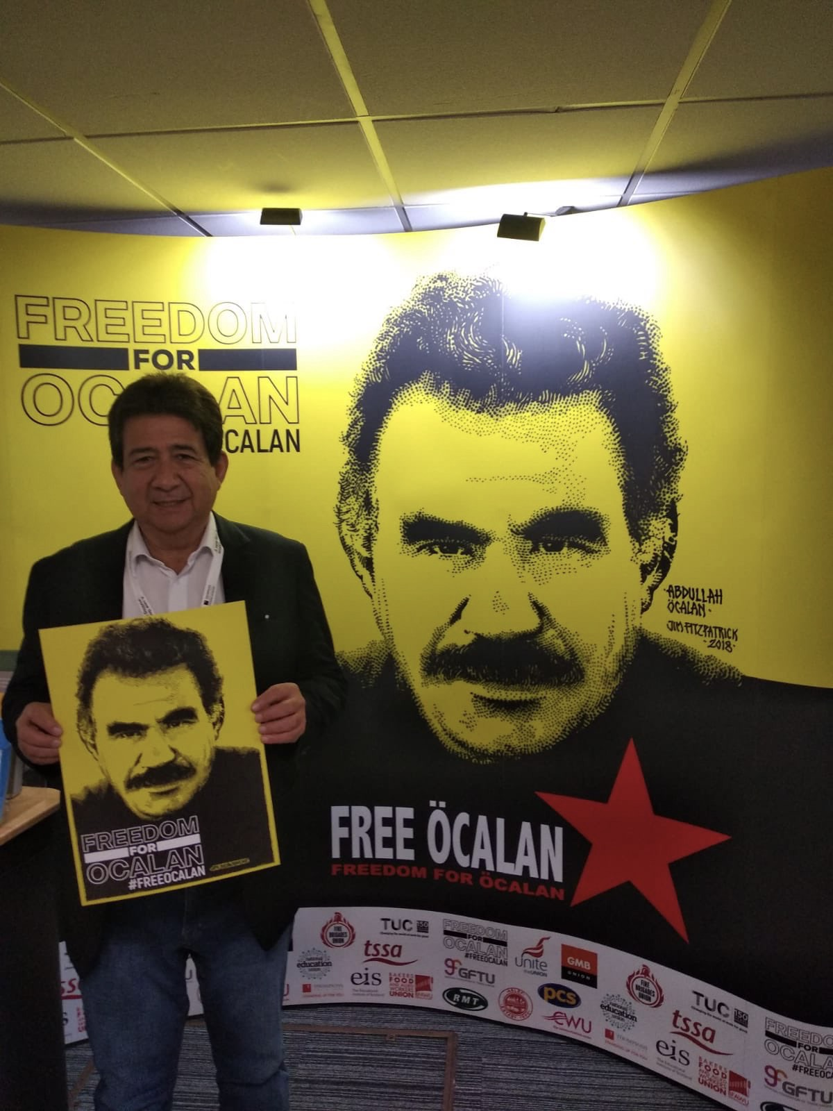 Diogenes Orjuela President CUT Columbia holidng placard calling for Freedom for Ocalan at TUC Congress 2019