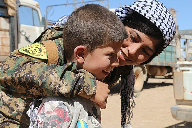 640px-A_YPJ_soldier_puts_her_arm_around_a_boy