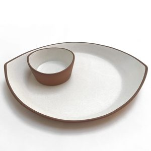 small white ceramic dish sitting on top of larger white ceramic platter