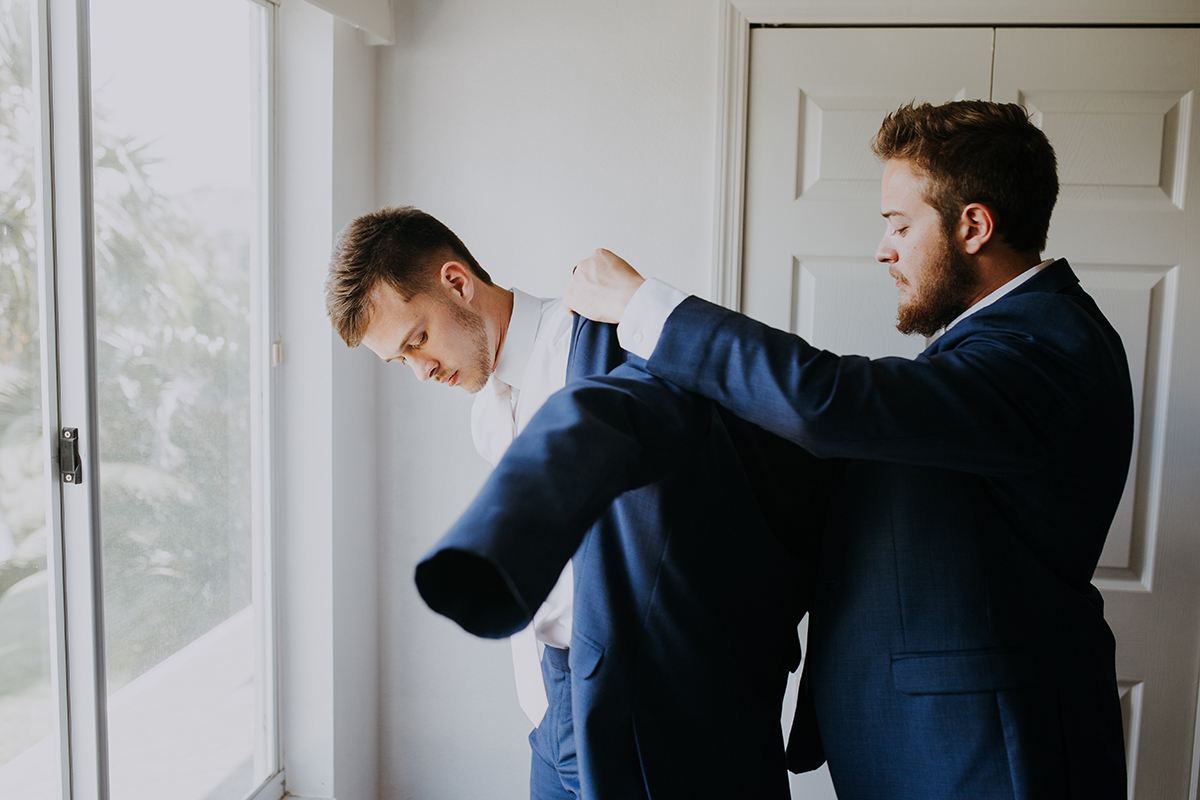 groom getting ready | putting on the suit jacket | groom and best man