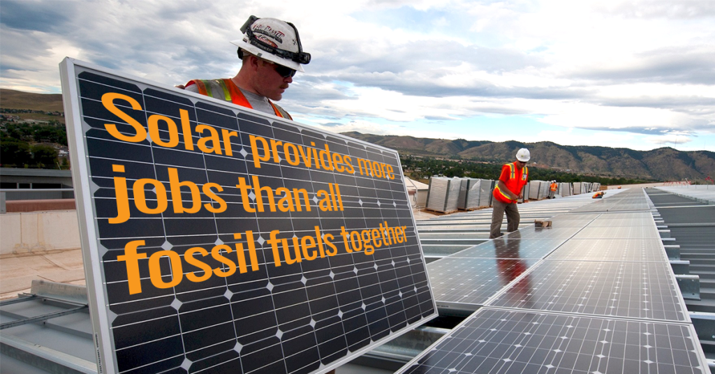 "Solar workers on a roof holding a panel that says ""solar provides more energy jobs than all fossil fuels together"""