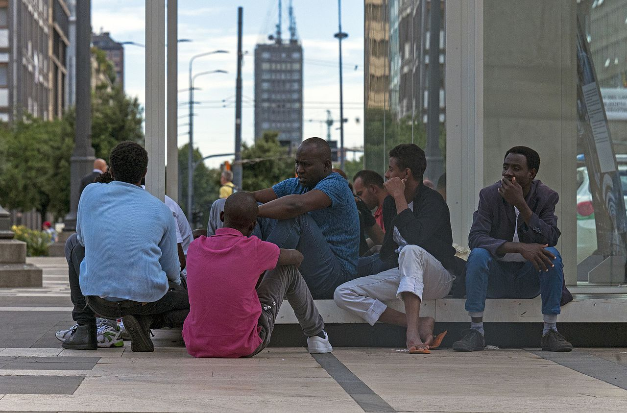 Daniel Case: African men sitting on the Piazza duca d'Aosta, Milan