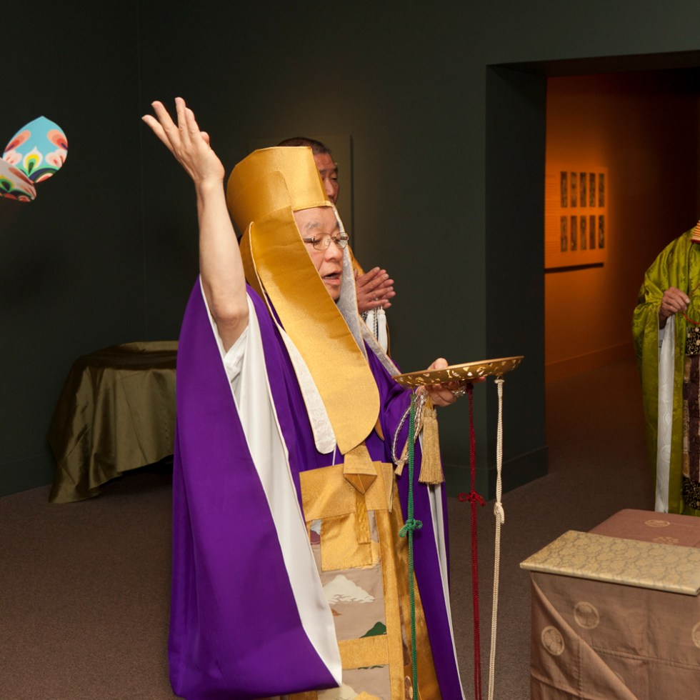 Person in purple and gold robes wth right hand in the air.