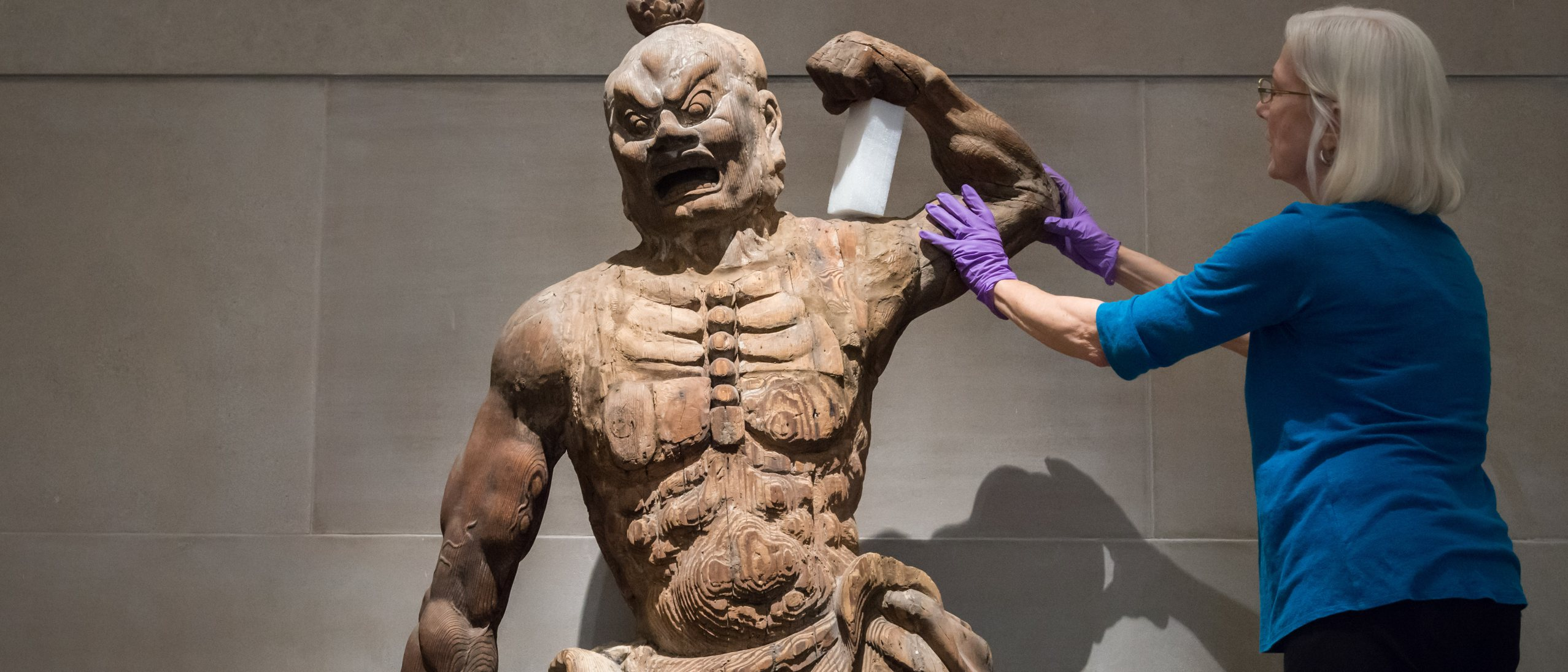Conservator repairing the arm of a wooden guardian statue