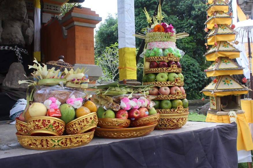 Ceremonial offerings in front of sculptures of deities at Candi Puser Ing Jagat in Pejeng village