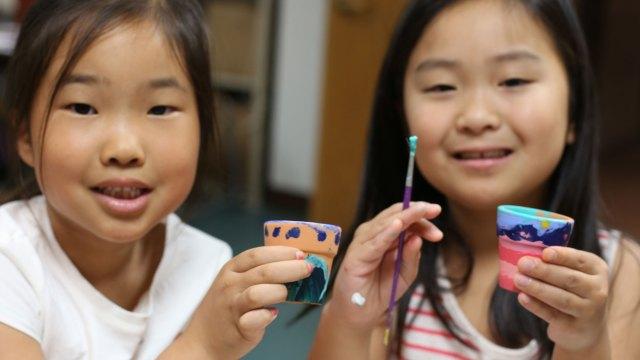 Two children show off their crafts