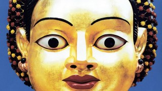 Gilded face of Devi with wide eyes, red lips, bright blue background.