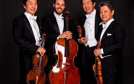 Four men dressed in white and black tuxedos are holding their instruments. Three have violins and one has a cello.