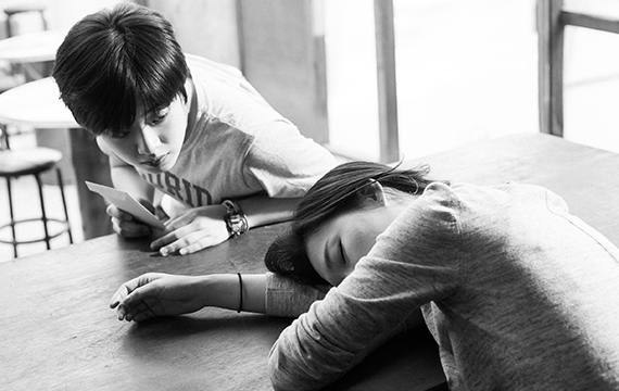 A girl asleep on a table and a boy (sitting at the same table) is looking at her.
