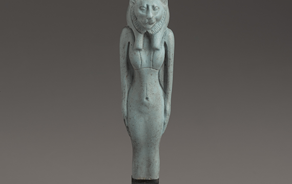 A greenish-grey Egyptian statue that is half human and half cat.