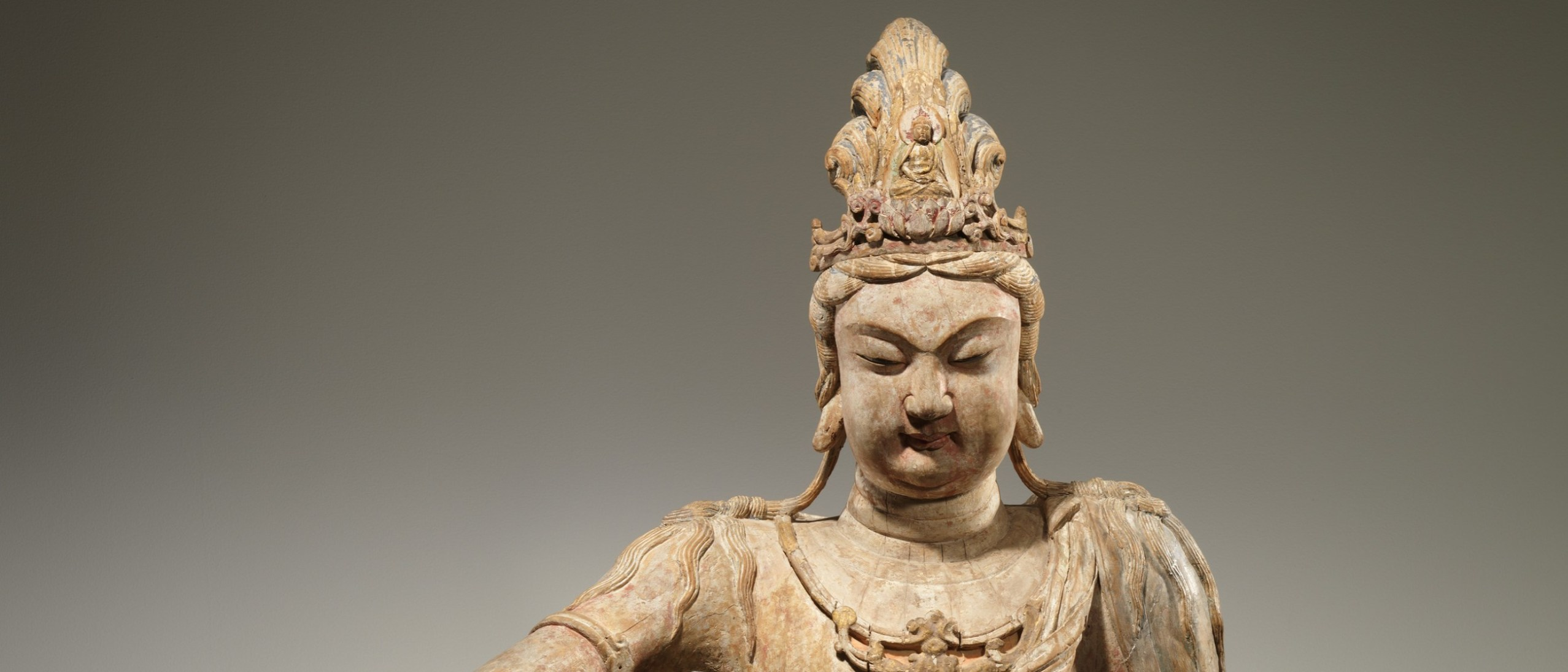 Head and shoulders detail of female bodhisattva, Guanyin, wearing an ornamental headdress.