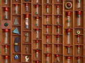 Segmented drawer containing fragments of colored glass and beads.