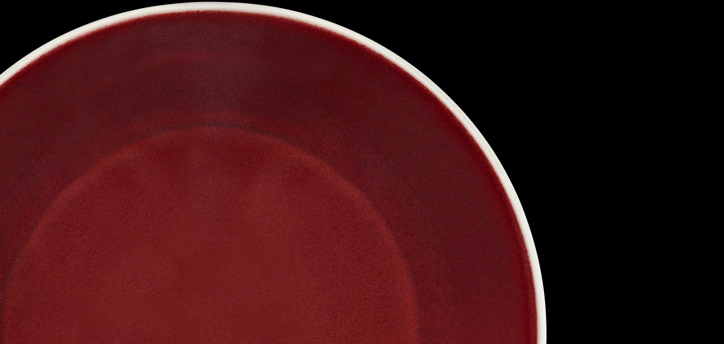 Scarlet bowl with white lip stands out against black background.
