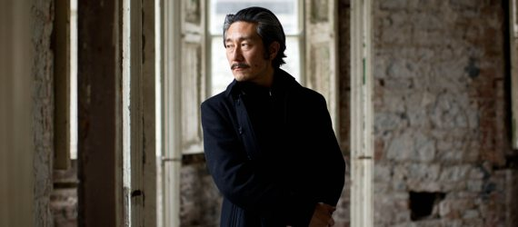 Artist standing in corridor, looking pensively to the left.