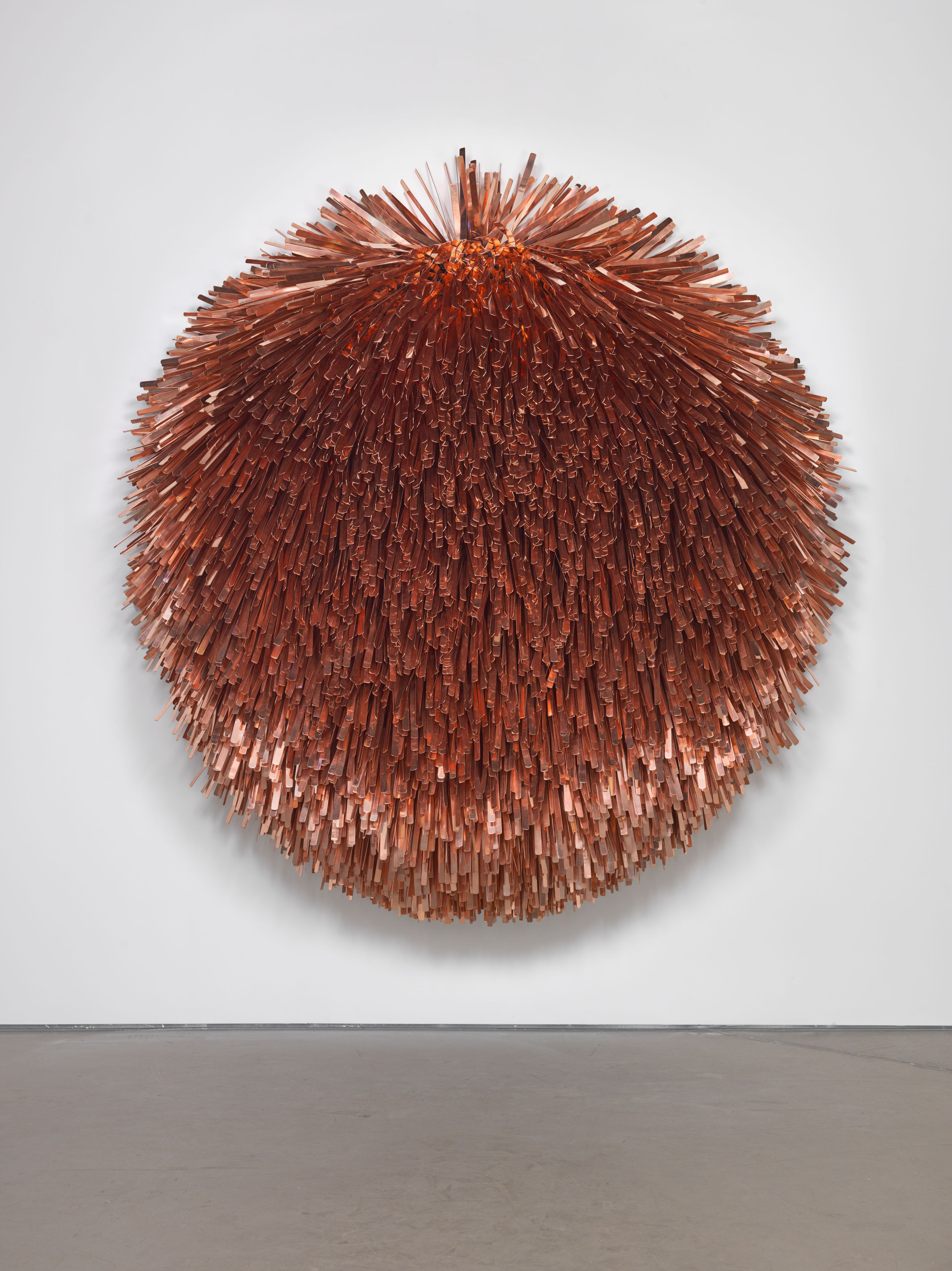 A fringed coppery-orange, circular sculpture