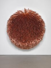 A fringed coppery-orange, circular sculpture