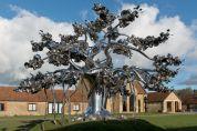 A metal tree standing beneath a blue sky near some houses