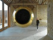 a large round brass sculpture hangint from the wooden rafters of a stone building. A person walks in the background.