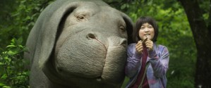 still from film, Okja. giant pig standing next to young female in purple jacket