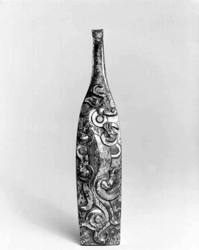 Photo, Bronze garment hook with glass and silver inlay. Eastern Zhou dynasty, 3rd century BCE., L: 15.2 cm. (5 5/16 in.) Singer catalogue number: [670].