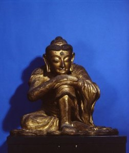 Buddha seated with his chin on his knee