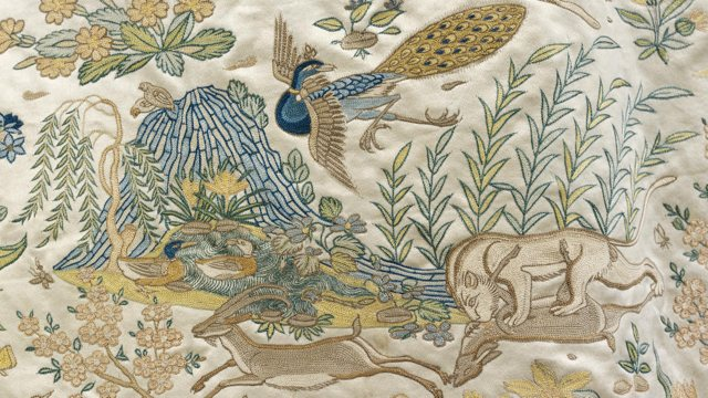 embroidered depiction of bird in flights, and lion-like animal attacking a gazelle. mountain and vegetation in background