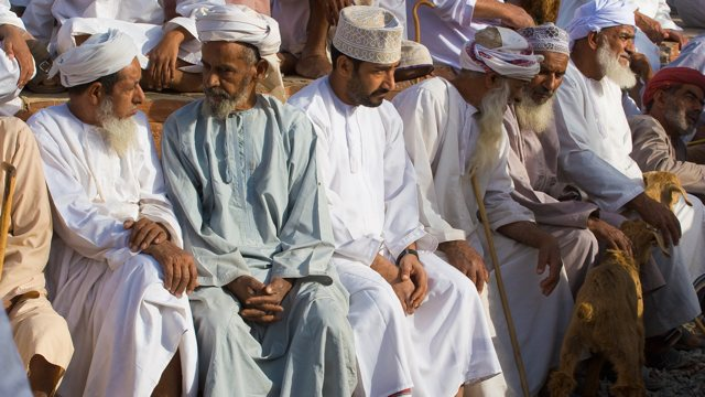 several men seated. wearing white and light-colored clothing