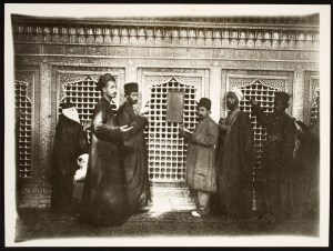 Five men and a woman in dark clothes, and a child in white stand in front of a shrine, turned sideways to peer at the camera.