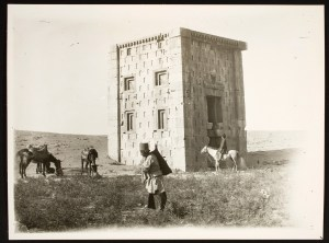A man walks in the foreground in front of a tower in the desert, while three horses graze on one side, and a man astride a white horse looks up at the tower.