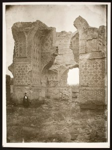 A figure is dwarfed by the enormous stone archways he stands in front of.